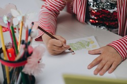 Hands of kid who is involved by drawing. Creative hobby, lifestyle drawing. Artist concept. Talented Innovative Female Artist Draws with Her Hands.