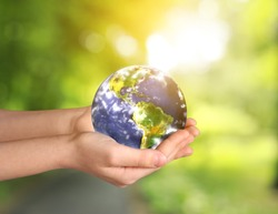 Hands of little child with planet on blurred background. Earth Day celebration