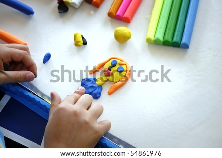 Hands of little girl making doll from colorful clay dough  (plasticine) 1