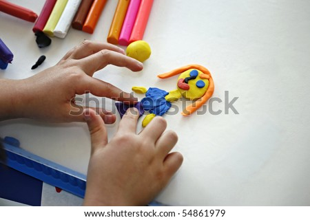 Hands of little girl making doll from colorful clay dough  (plasticine) 2