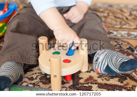 Hands of Little toddler boy playing with wooden toys indoor
