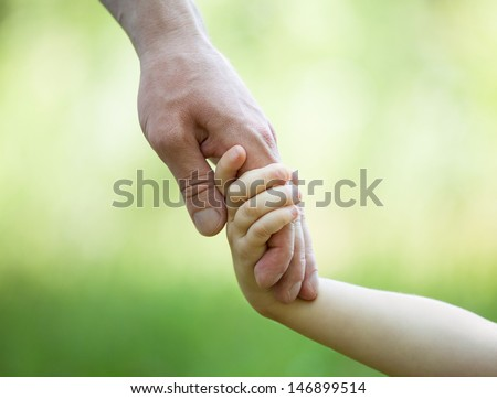 Hands of man and child holding together on light green background