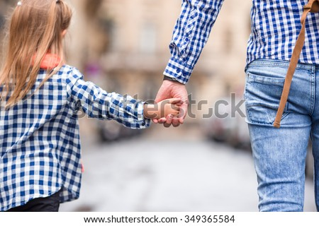 Hands of man and child holding together on street at european city