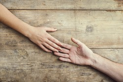 Hands of man and woman holding together tenderly. Studio shot on a wooden background, view from above.