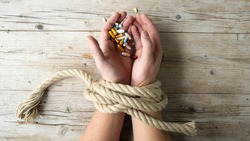 Hands of man are tied with a rope and in his hands he holds many different pills, concept addiction, drug addiction, photo taken from above