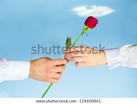 Hands of man giving rose to woman on blue sky background