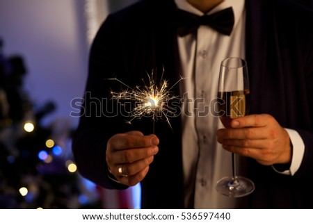 Hands of man holding Bengal light at the party. Sparkler - New Year's Eve. Party, holidays, nightlife and people concept  #536597440