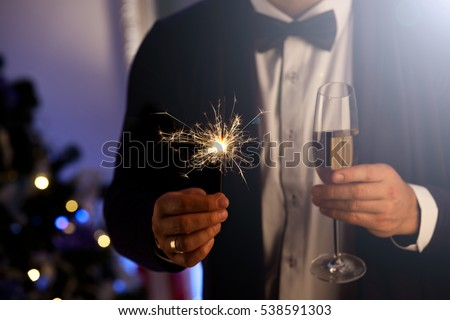 Hands of man holding Bengal light at the party. Sparkler - New Year's Eve. Party, holidays, nightlife and people concept  #538591303