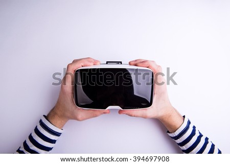 Hands of man holding virtual reality goggles. Flat lay