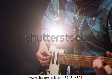 Hands of man playing electric guitar. Bend technique.