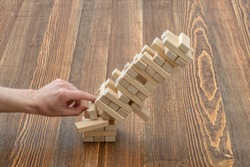 Hands of man pushed the brick and destroyed the tower. Janga. Close-up photo. Imbalance. Collapse and destruction. Mistake. Entertainment activity. Game of physical and mental skill. Removing blocks