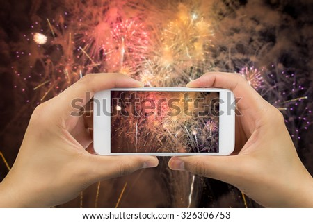 hands of man taking the photo to fireworks with the new smart phone
