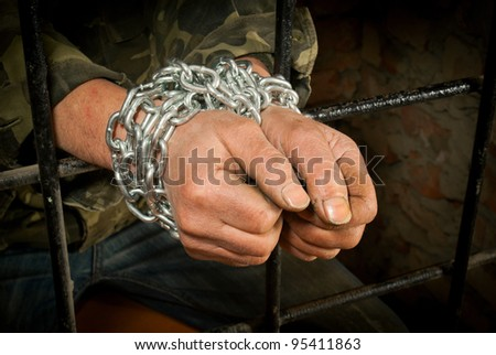 Hands of man tied up with chain behind bars