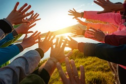 Hands of many friends reaching together for the sun. Friendship or travel concept