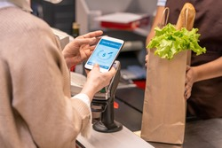 Hands of mature female buyer with smartphone over payment machine going to pay for food products in supermarket by cash register