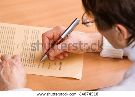 Hands of mature woman signature document sitting on desk