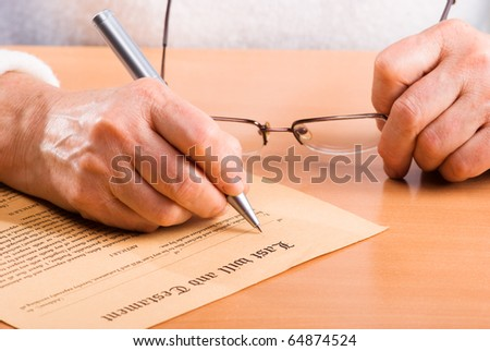 Hands of mature woman signature Last Will sitting on desk