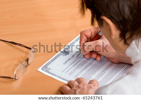 Hands of mature woman signing Last Will sitting on desk