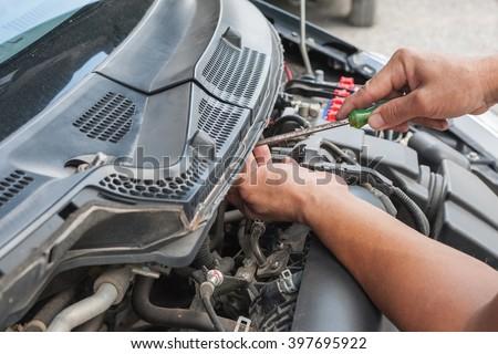 Hands of mechanic working in auto repair shop #397695922