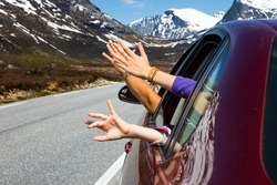 hands of men and children peering out of the car on a background of mountains, norway