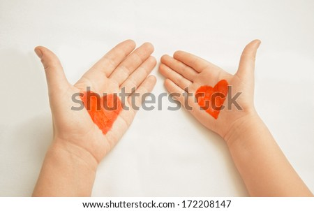 Hands of mother and child painted with red hearts concept of love