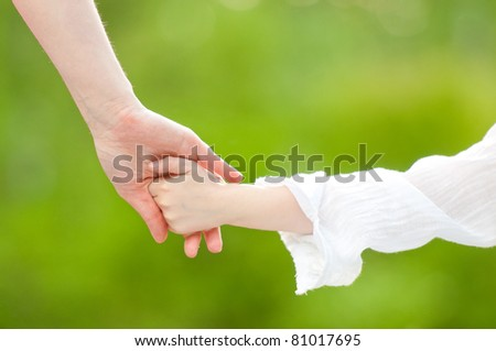 Hands of mother and daughter holding each other. Summer park in background