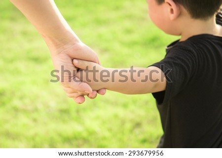 Hands of mother and son holding each other. Summer park in background