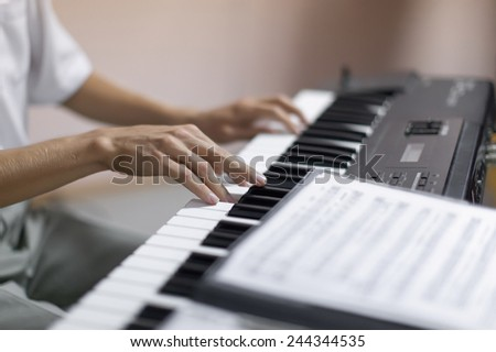 Hands of musician. Pianist playing on a synthesizer indoor. Shoot with shallow depth of field