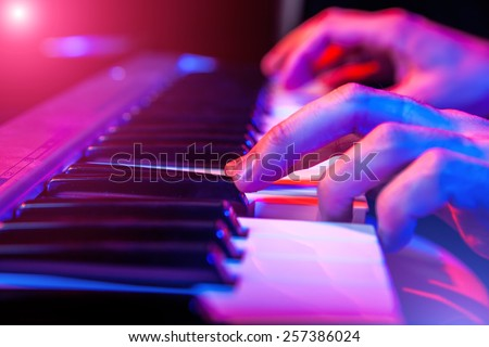hands of musician playing keyboard in concert with shallow depth of field #257386024