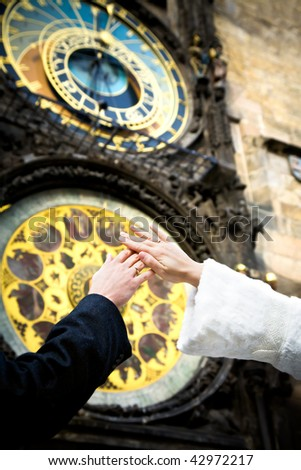 hands of newly married on clock background on the wall of Old Town City Hall in Prague, Czech Republic