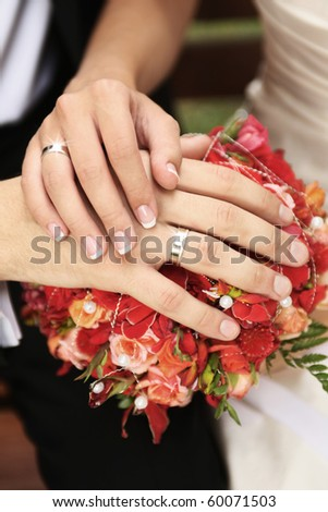 hands of newly wedded couple with shiny rings on bouquet