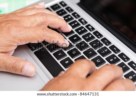 Hands of old man on computer