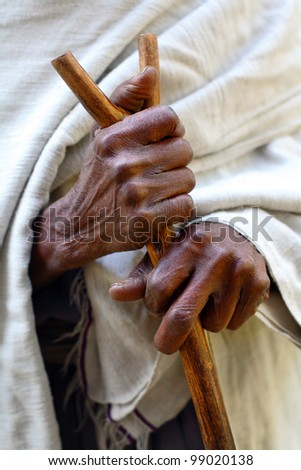 Hands of old woman, close-up with stick - stock photo
