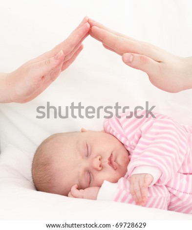 hands of parents combined by a small house over the sleeping baby. The concept of care of children.