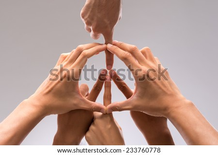Hands of people forming a symbol of peace
