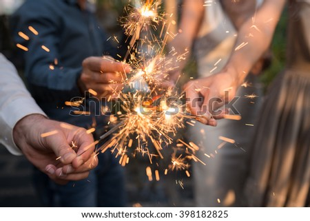 Hands of people holding Bengal light at the party #398182825