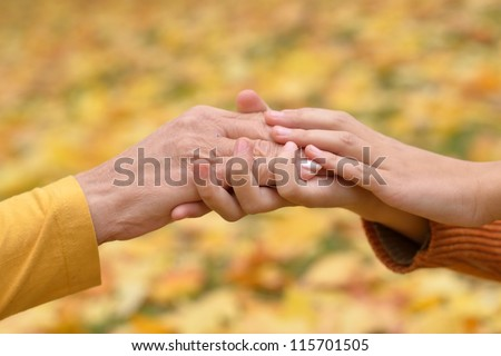 hands of people of different ages in the autumn park #115701505