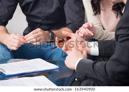 Hands of people signed the document, sitting at the desk