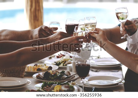 Hands of people with glasses of champagne or wine, celebrating and toasting in honor of the wedding or other celebration.