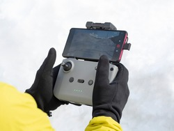 Hands of person in gloves holding wireless remote control of drone with phone