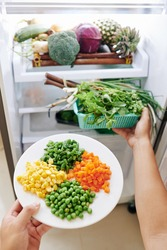 Hands of person opening fridge taking out plate with corn, diced carrot, pea and grean beans