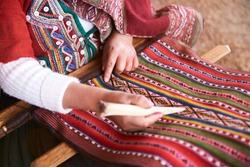 Hands of peruvian woman making alpaca wool close-up. Manufacture of wool material in Peru