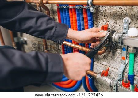 hands of plumber working in boiler room