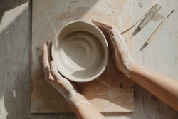 Hands of potter do a clay pot. Top view.