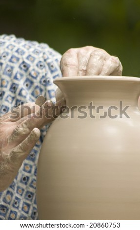 hands of potter finishing tall vase on wheel - stock photo