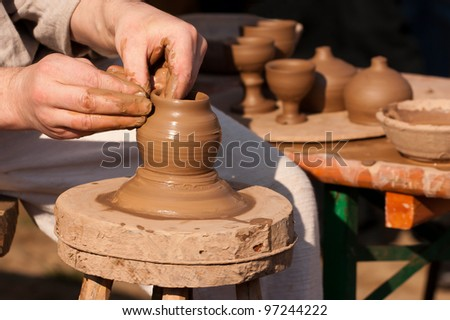 Hands of potter shaping clay on wheel