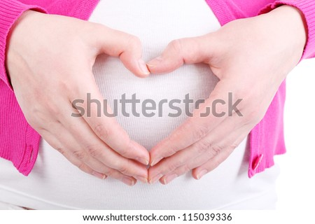Hands of pregnant woman wearing in pink blouse depicting heart on her stomach isolated on white background.