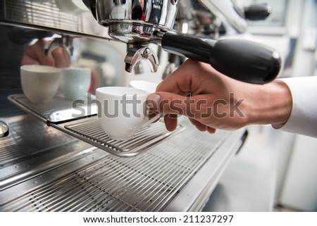Hands of professional barista holding two white cups on the grating of coffee machine