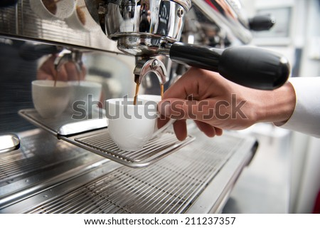 Hands of professional barista holding two white cups on the grating of coffee machine looking how coffee pouring into them