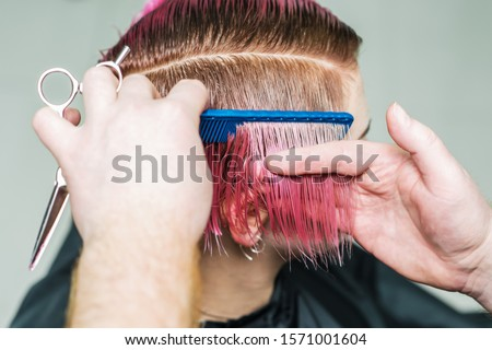 Hands of professional hairdresser combing pink short hair close up.